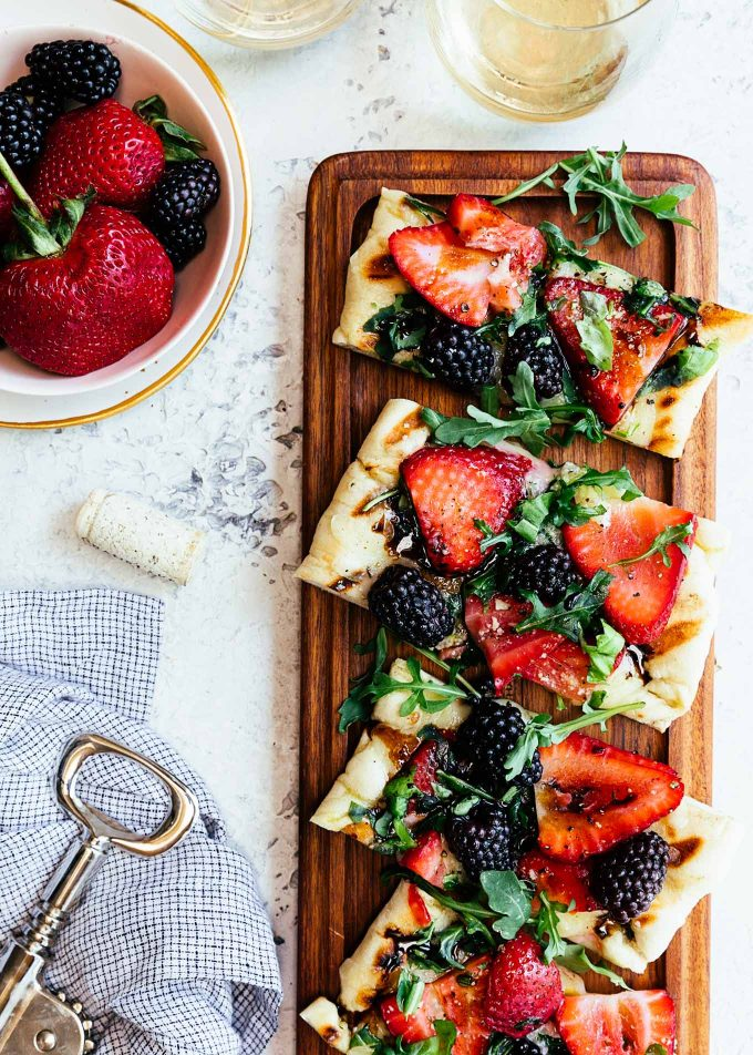 grilled pizza with summer berries and arugula on a wood serving board {sponsored}