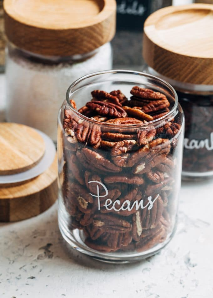 pecans in wood-topped glass jars