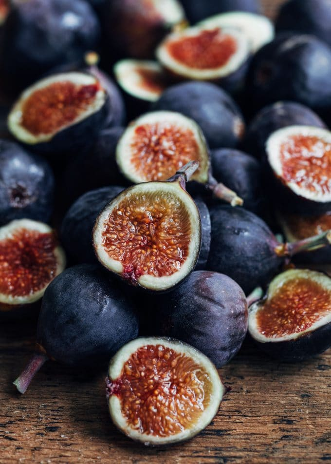 whole and halved figs on a wood board