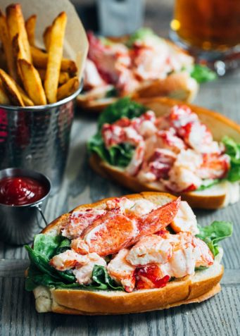 maine lobster rolls on a wood board with french fries