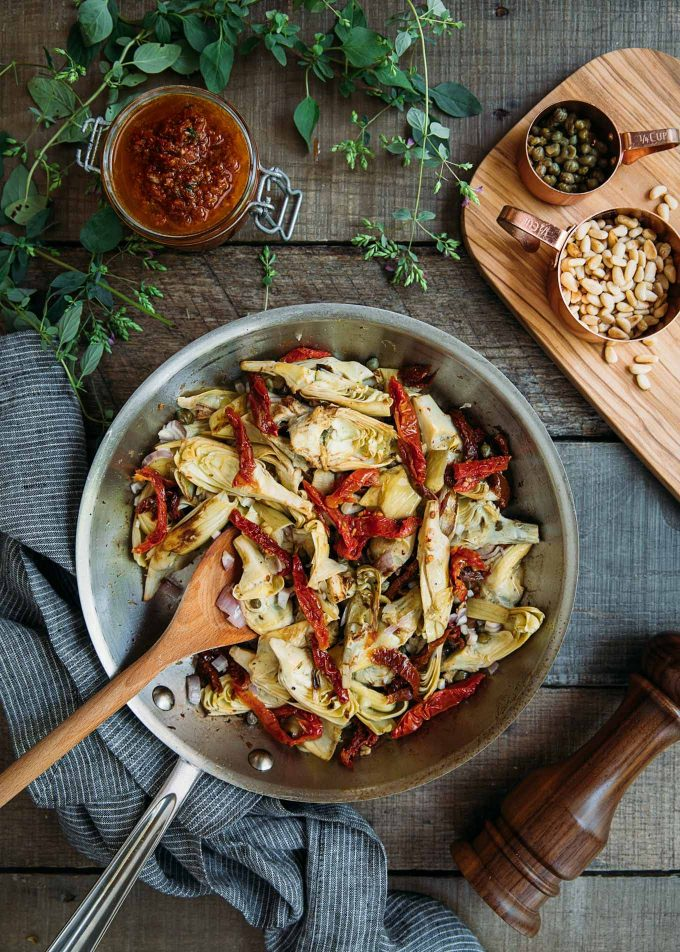 sauteed artichokes and sun dried tomatoes in a saute pan
