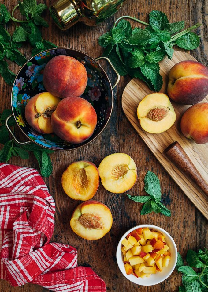 whole and cut peaches on a board with mint leaves