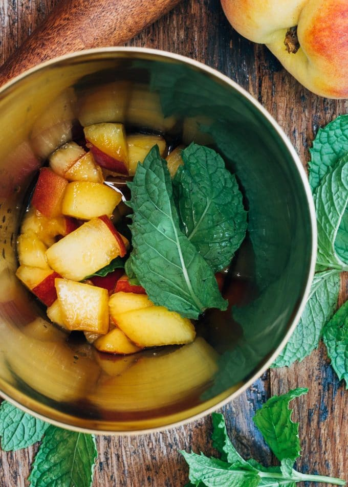 peaches and mint leaves in a cocktail shaker for a bourbon smash cocktail