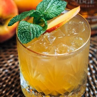bourbon peach smash cocktail with mint