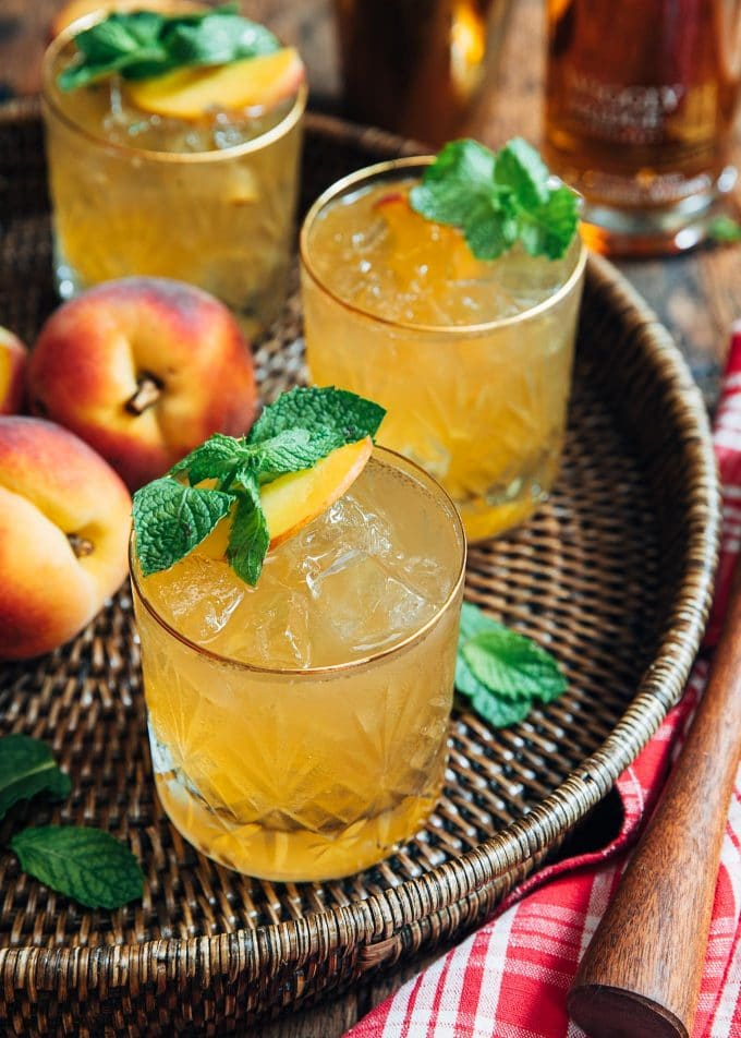 peach bourbon cocktails on a wicker serving tray