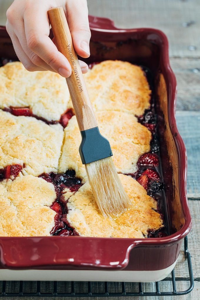 brushing cornbread biscuits on baked berry cobbler with honey butter
