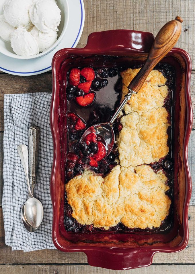 mixed berry cobbler in an emile henry baking dish with a bowl of ice cream