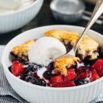mixed berry cobbler with cornbread biscuit topping and vanilla ice cream in a bowl