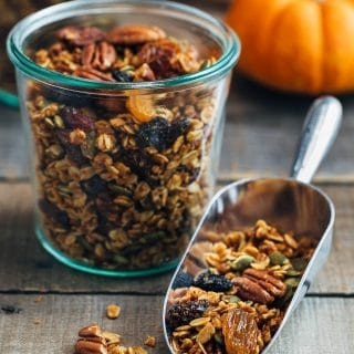 pumpkin granola in a scoop and glass storage jars
