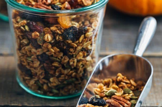 pumpkin granola in a scoop and glass storage jars