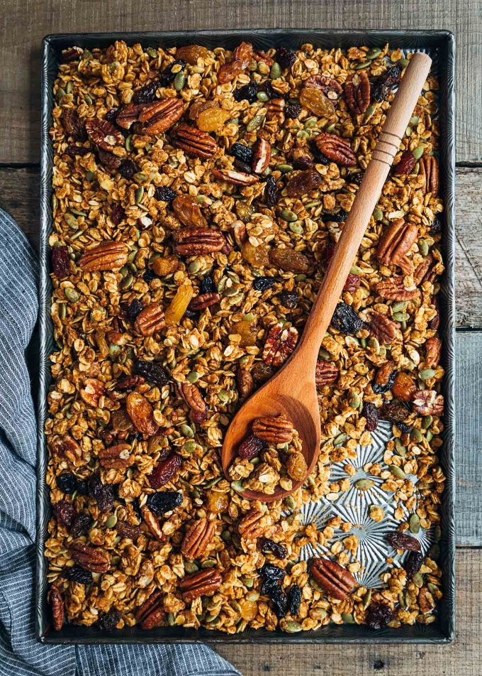 baked pumpkin granola on a sheet pan with a wooden spoon