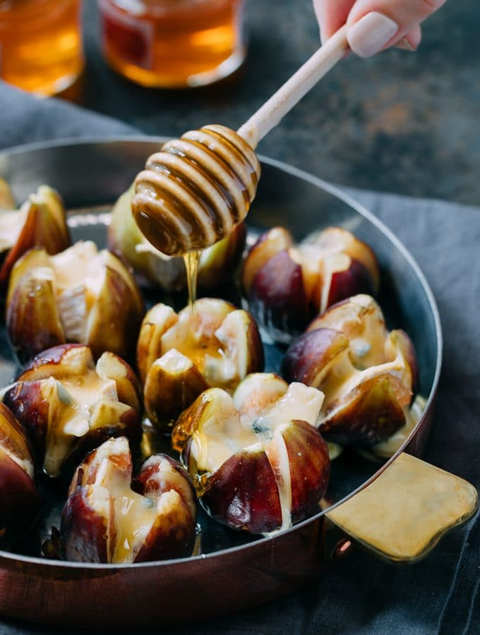 drizzling honey over baked Cambozola stuffed figs with a honey dipper