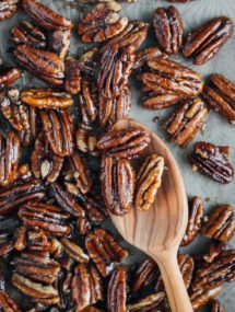 caramelized pecans on a baking sheet with a wooden spoon