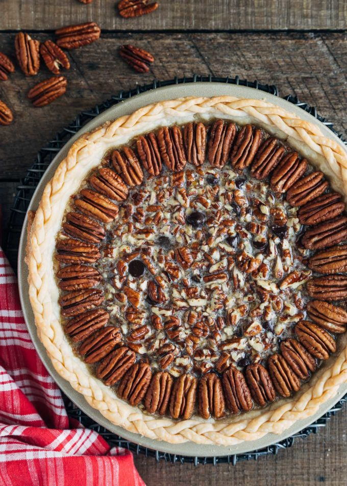 unbaked chocolate pecan pie on a wood board with a red plaid napkin