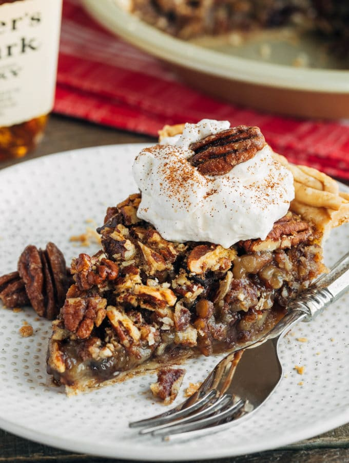 slice of chocolate pecan pie on a plate with whipped cream