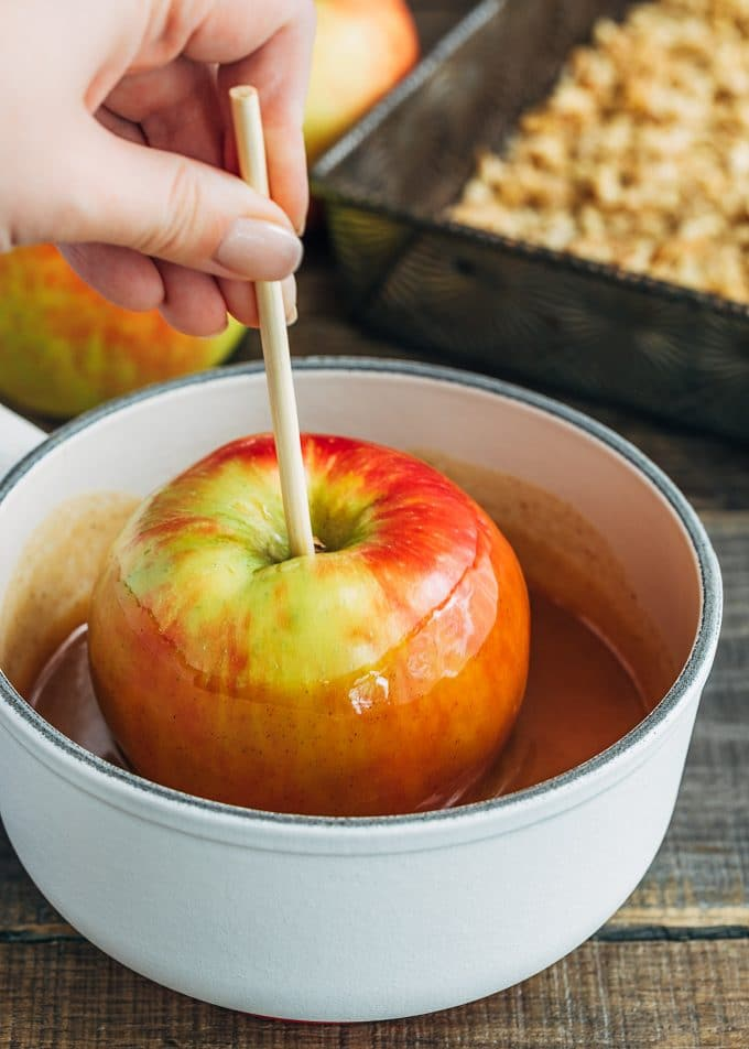 hand holding a honeycrisp apple on a stick in a pot of caramel