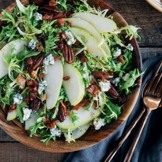 pear salad with warm bacon vinaigrette in a wooden bowl