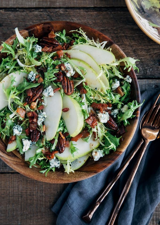pear salad with blue cheese and warm bacon vinaigrette in a wooden bowl