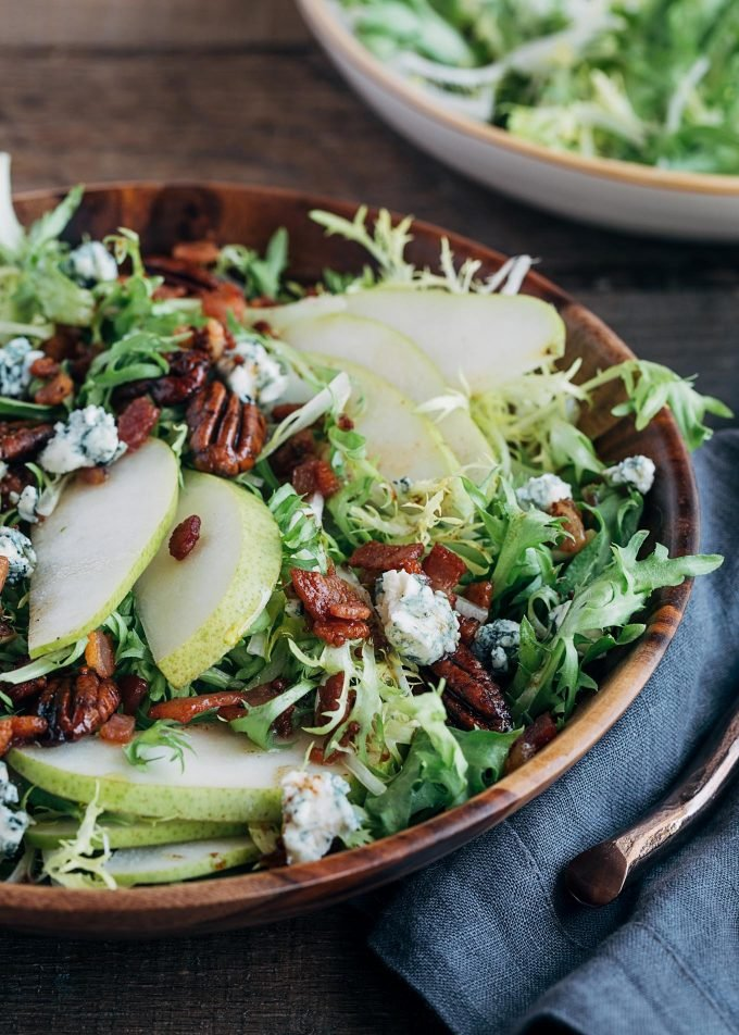 frisee salad with pears and warm maple bacon vinaigrette in a serving bowl