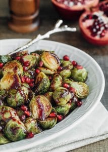 roasted brussels sprouts with pomegranate in a white serving dish