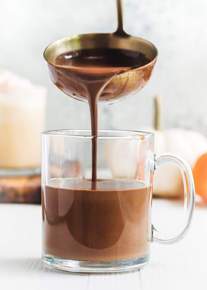 pouring dark chocolate pumpkin spice hot chocolate with a ladle