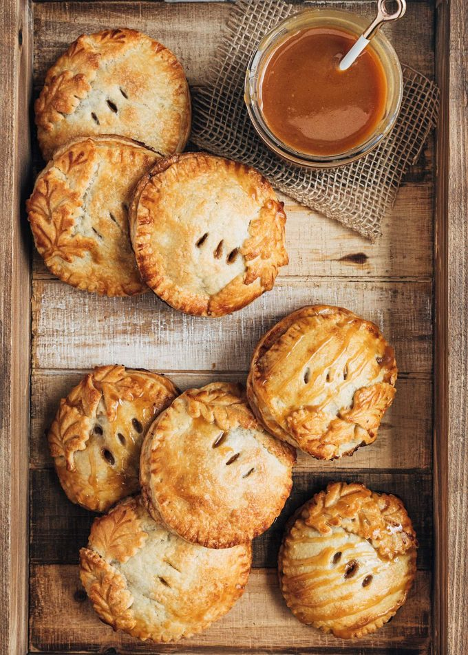 caramel apple hand pies on a wooden serving tray with a bowl of caramel sauce