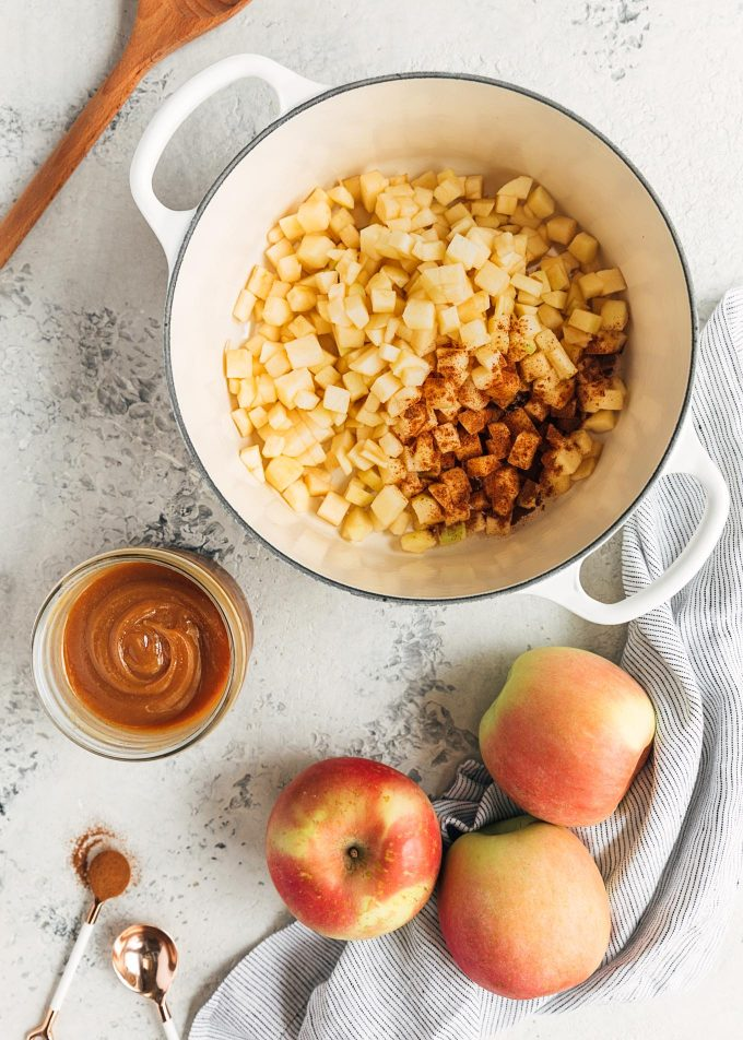 diced Fuji apples in a pot with a bowl of caramel sauce and whole apples on the side