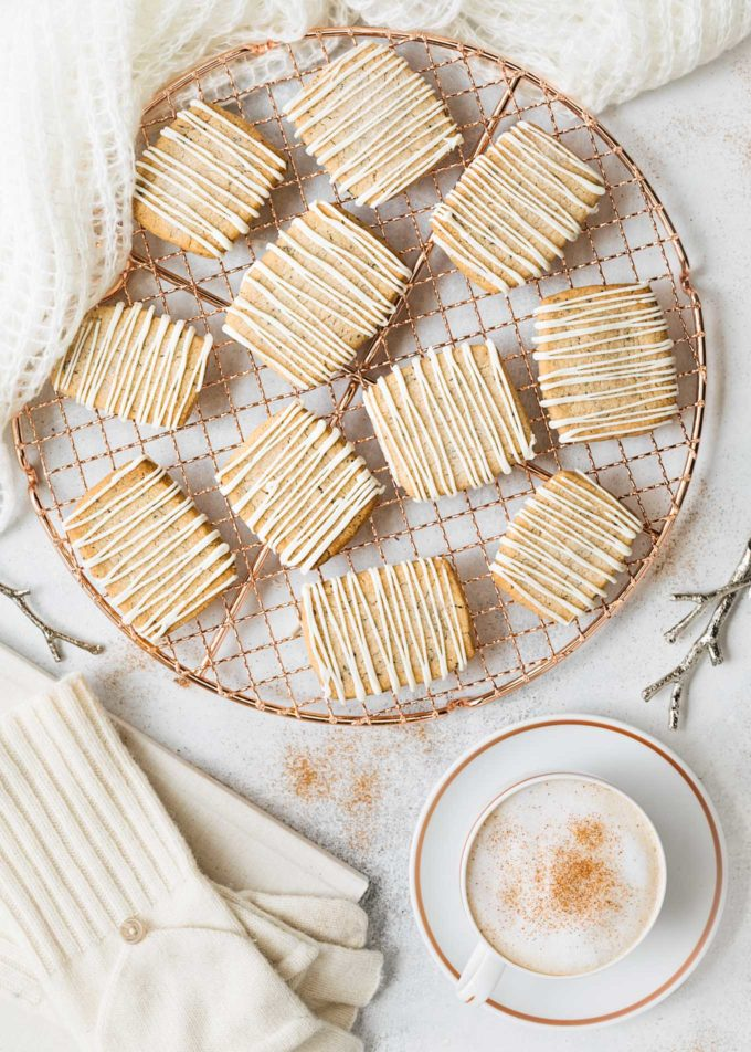 chai spice shortbread cookies with white chocolate drizzle on a cooling rack