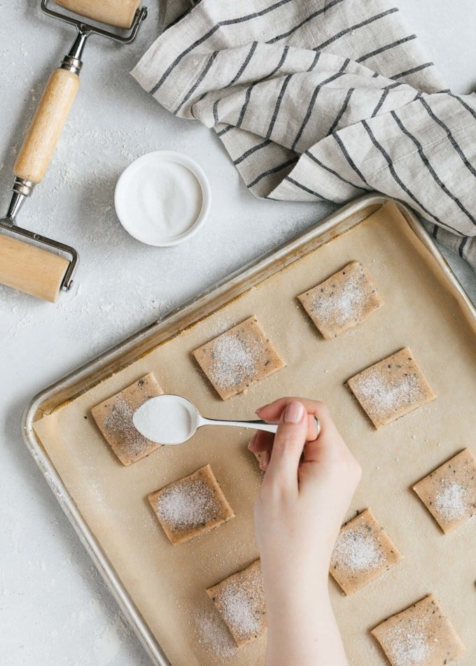sprinkling sugar onto unbaked chai shortbread cookies on a baking sheet