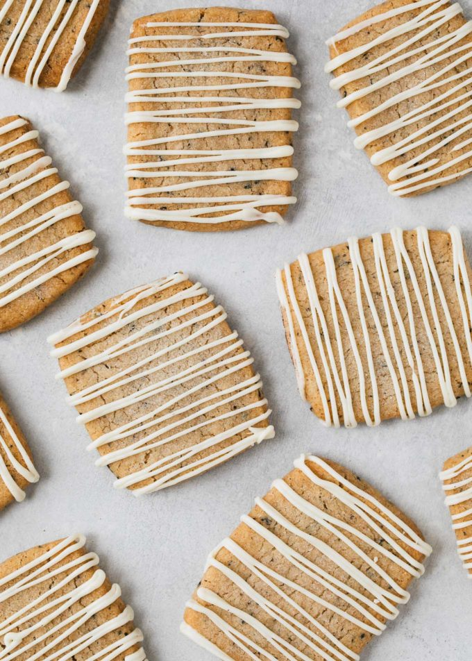white chocolate drizzled shortbread cookies on a baking sheet