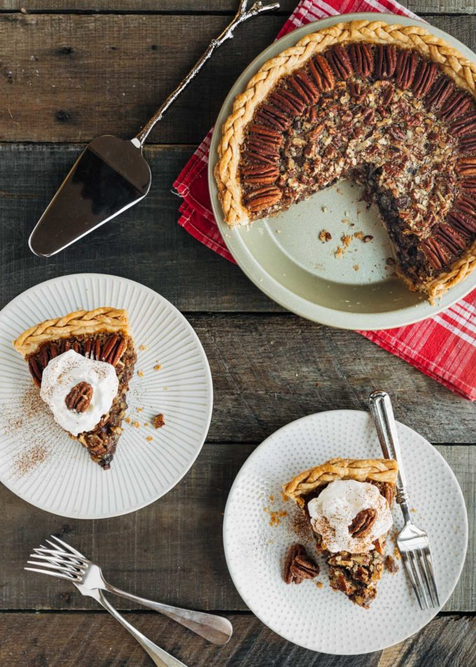slices of chocolate pecan pie with whipped cream on plates