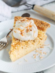 slice of coconut custard pie on a plate with whipped cream and toasted coconut flakes