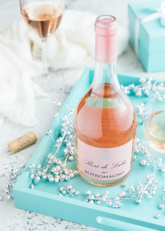 bottle of Botromagno 'Rose di Lulu' wine on a blue serving tray with silver bells