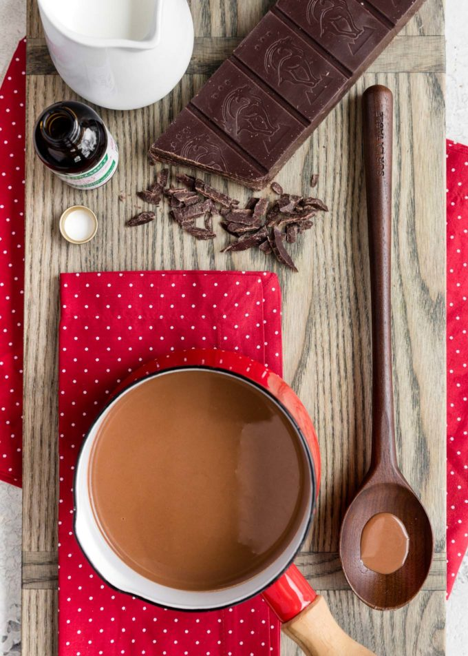 pot of peppermint hot chocolate on a board with a block of semisweet chocolate and a pitcher of milk