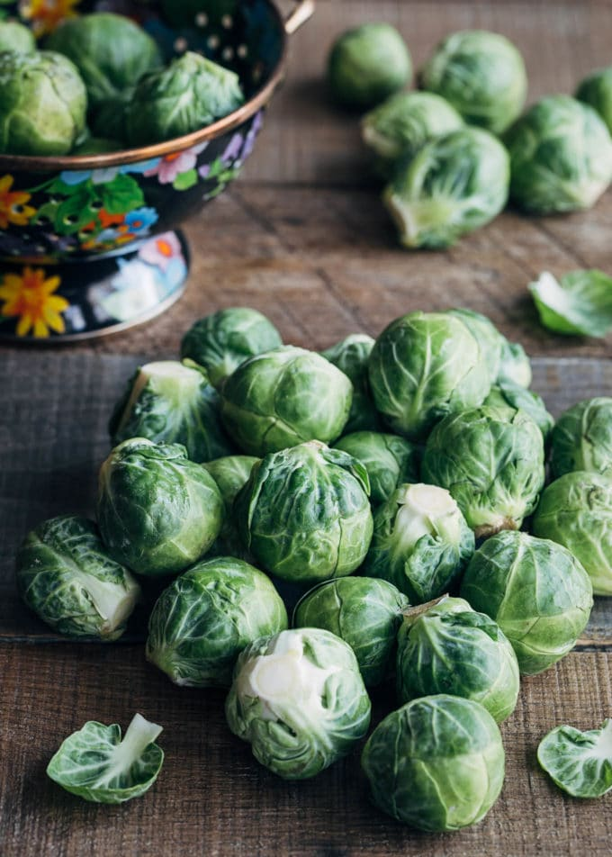raw brussels sprouts on a wood board with a colander