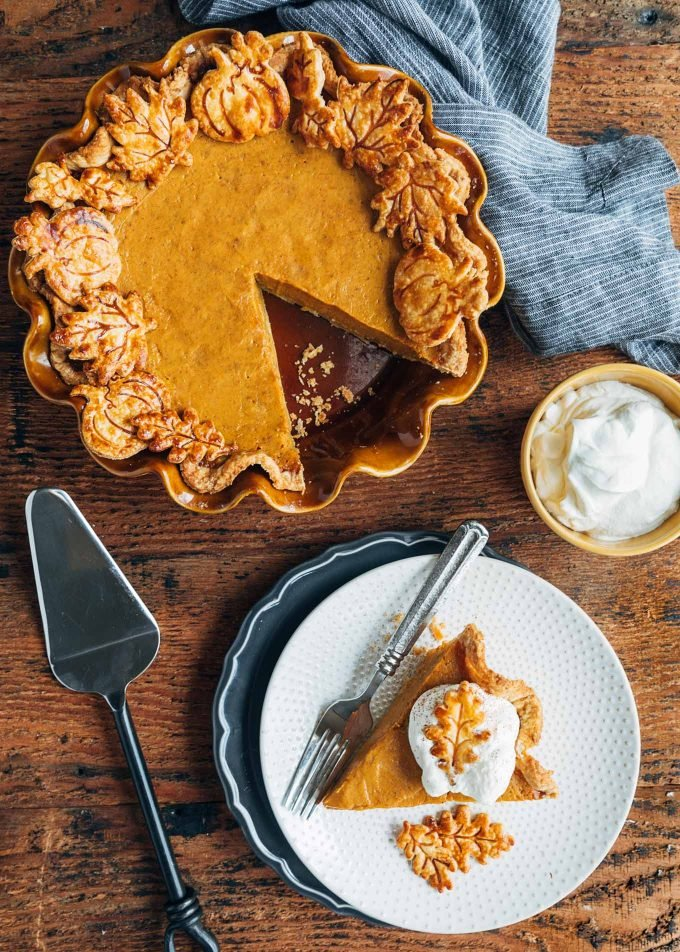 slice of pumpkin pie on a plate and a whole pie with a slice missing