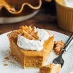 slice of pumpkin custard pie with whipped cream on a plate