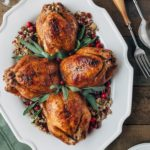 stuffed cornish hens on a white platter with fresh sage