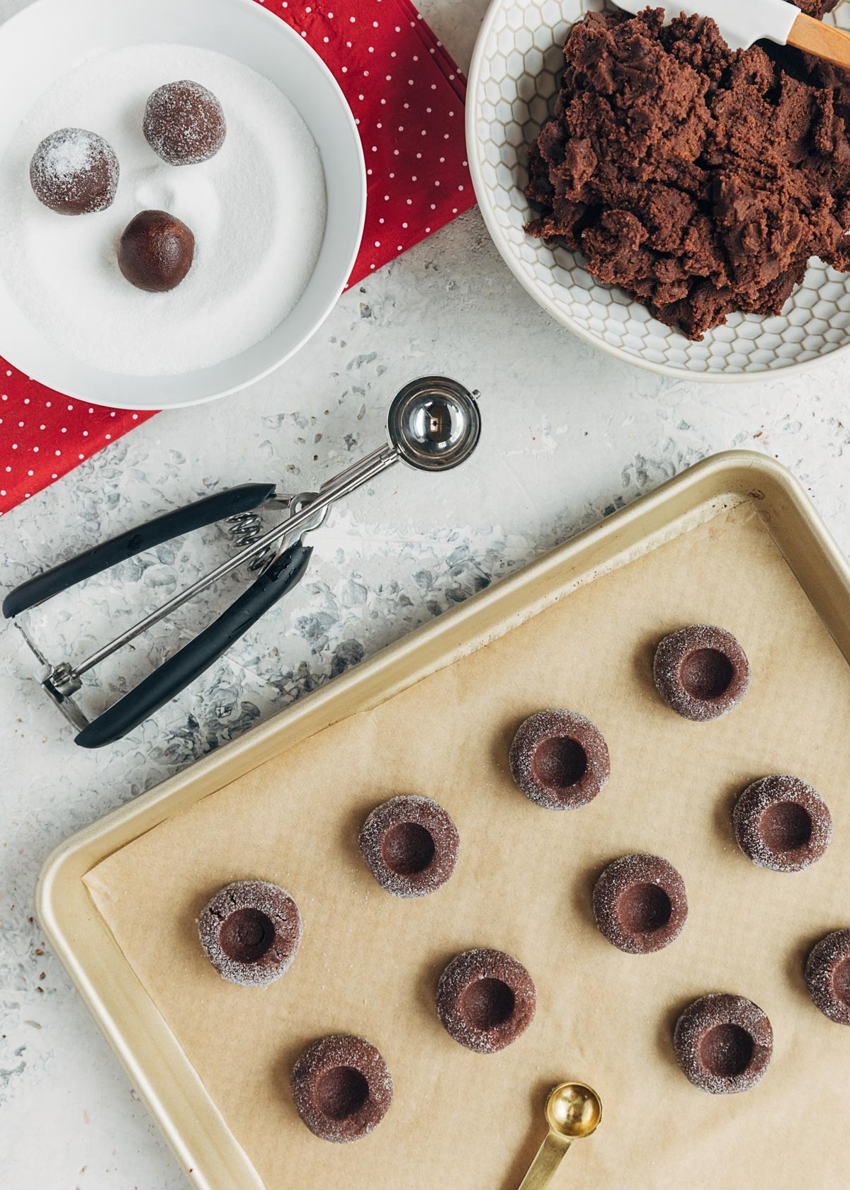 chocolate thumbprint cookie dough scooped onto a baking sheet