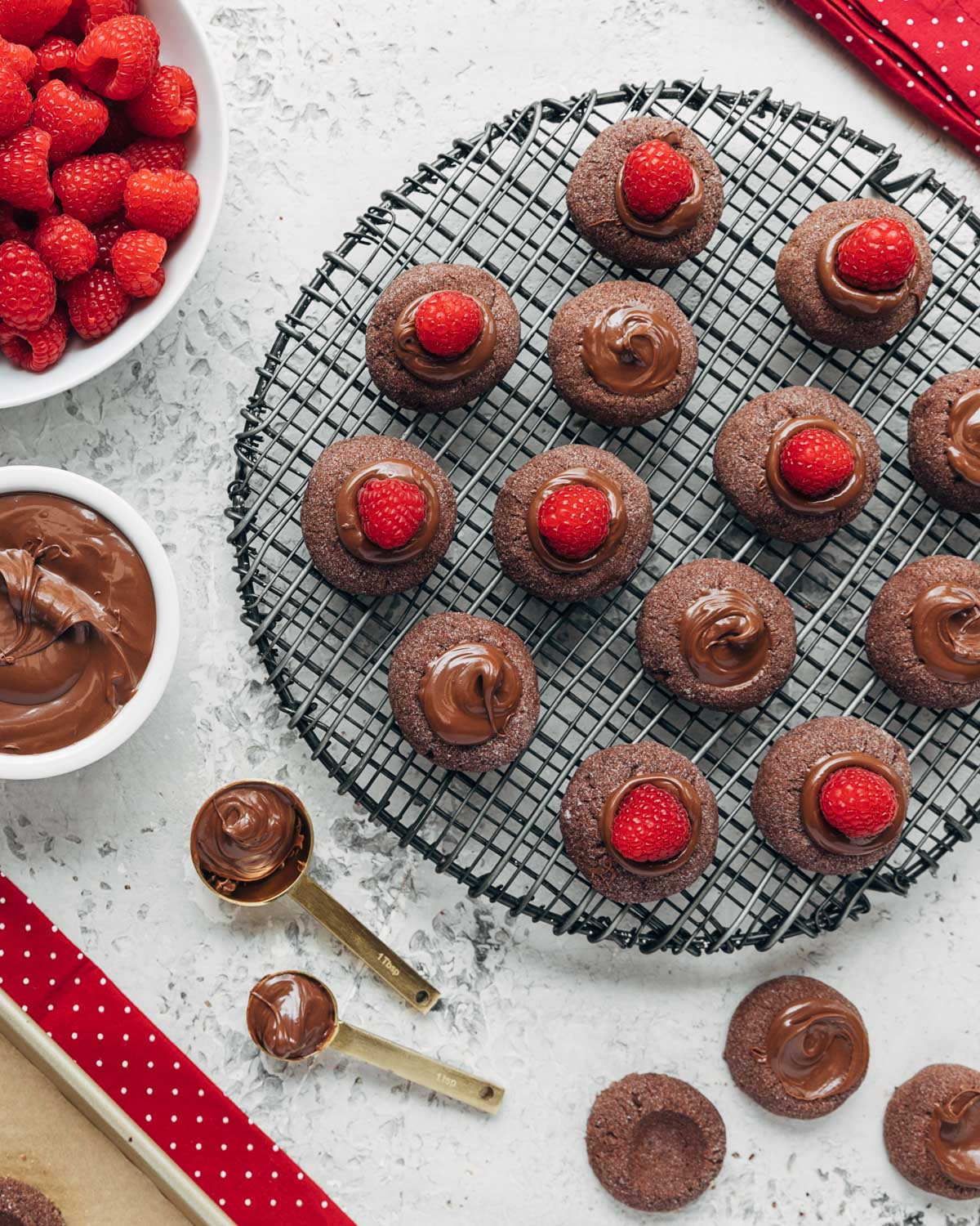 filled chocolate hazelnut thumbprint cookies on a cooling rack with bowls of raspberries and chocolate hazelnut spread