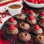 chocolate thumbprint cookies with raspberries and nutella on a cooling rack {sponsored}