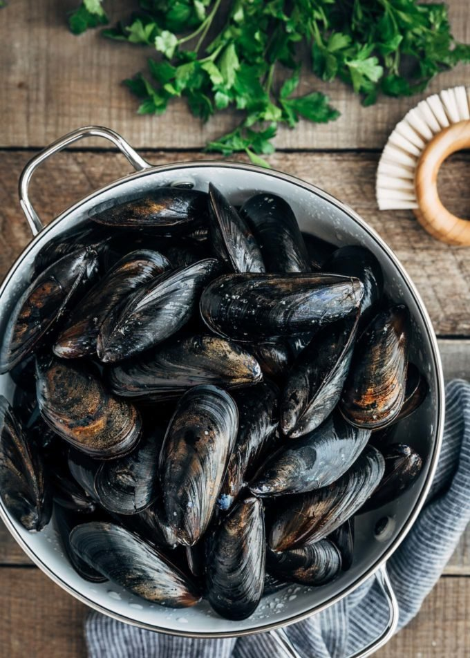 cleaned uncooked mussels in a colander with a brush on the board