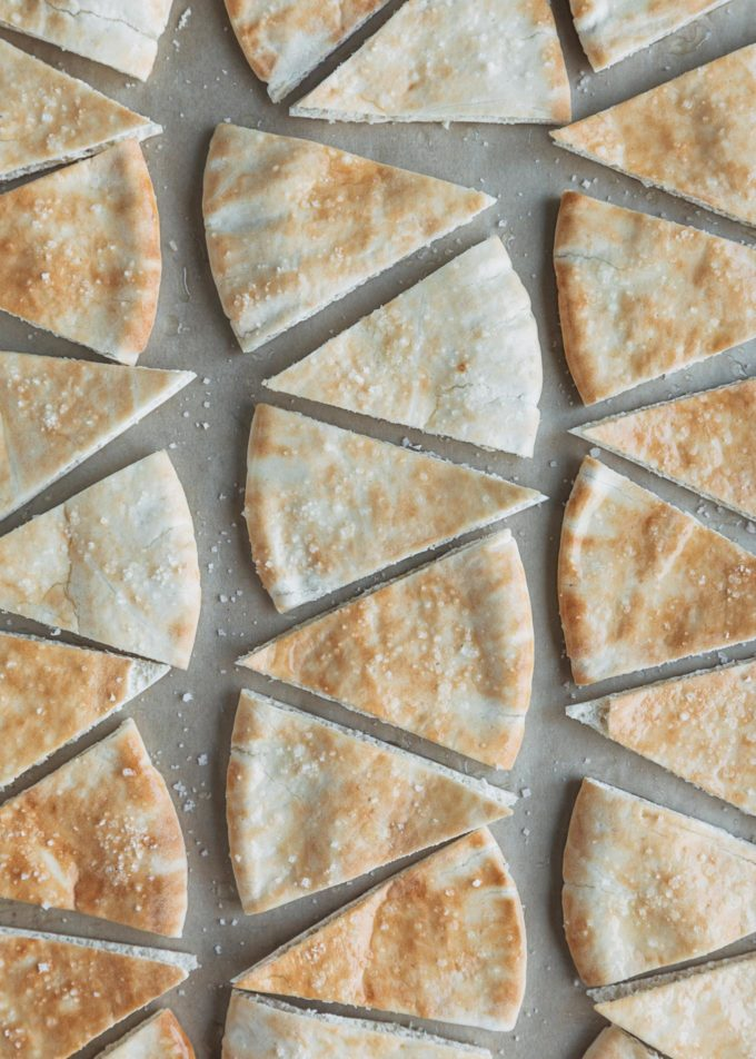 unbaked pita chips on a baking sheet with sea salt