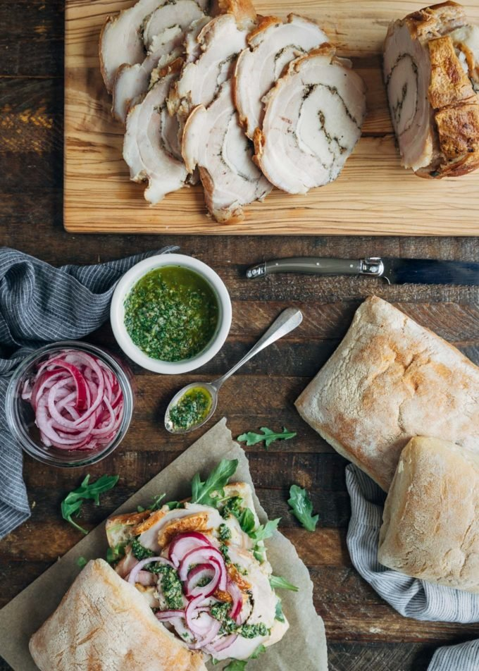 ingredients to make italian porchetta sandwiches on a wood board