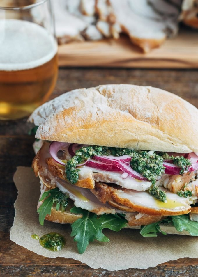 porchetta sandwich with salsa verde and pickled onions on a ciabatta roll
