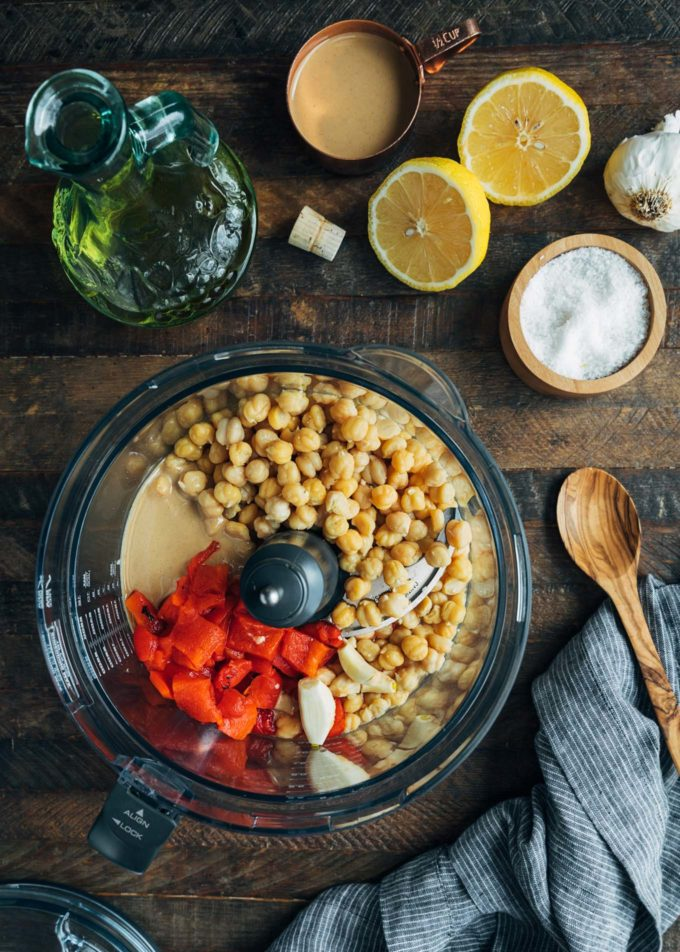 chickpeas, roasted peppers, tahini, and garlic in a food processor bowl for hummus