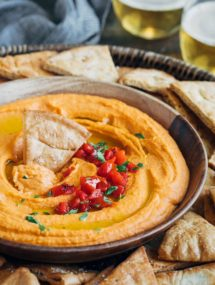 roasted red pepper hummus in a serving bowl with pita chips