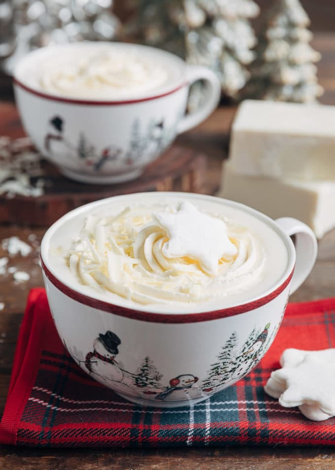 white hot chocolate in large mugs with whipped cream and snowflake shaped marshmallows