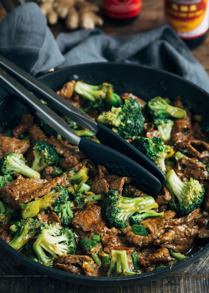 Beef and Broccoli stir-fry in a skillet with tongs