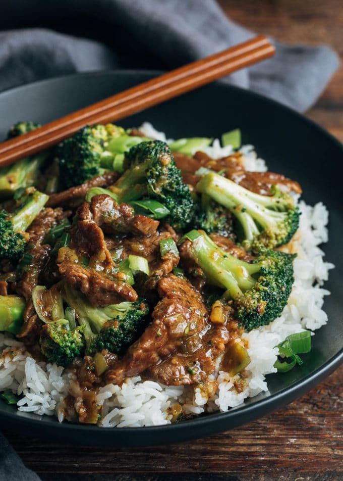 chinese beef and broccoli with rice in a black bowl